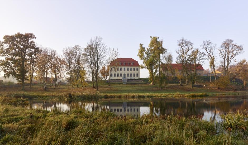 Gutshof Fredenwalde: Frontalansicht mit Wasser