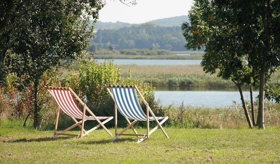 Gut Fergitz, zwei Liegestühle auf einer Wiese am See